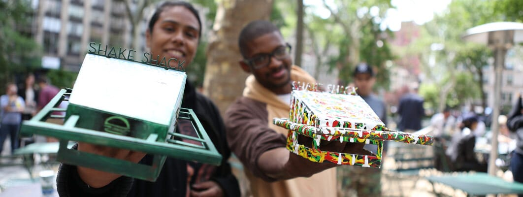 Two men holding customized cardboard models of Shake Shack buildings.