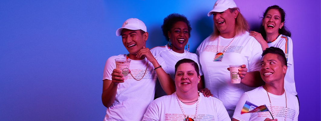 A picture of six people wearing the pride tee, necklaces, and drinking milkshakes while laughing.
